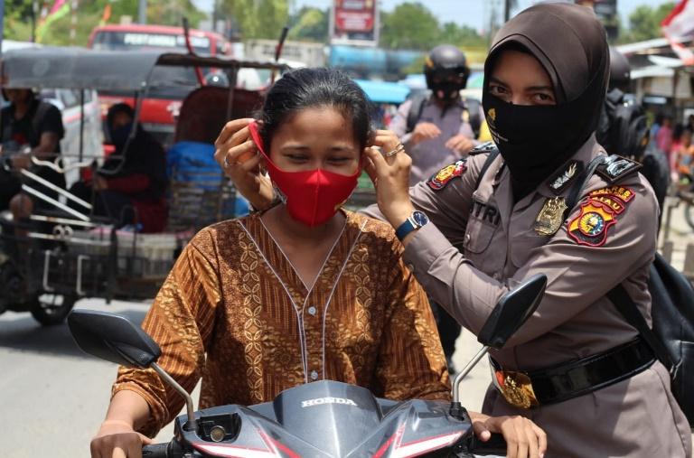 Polisi Wanita (Polwan) Polres Rohil sedang memasangkan masker kepada salah satu pengendara sepeda motor
